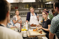 Female chef teaching students while standing at commercial kitchen - CAVF04516
