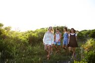 Friends walking on field against clear sky - CAVF04633