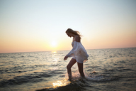 Side view of woman walking in water at beach against clear sky - CAVF04648