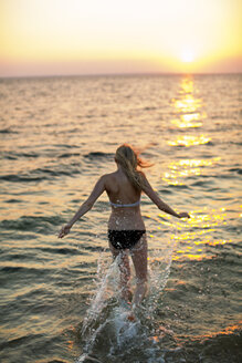 Rear view of woman running on shore at beach during sunset - CAVF04651