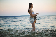 Side view of woman looking away while standing in sea - CAVF04657