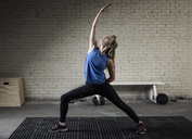 Woman practicing warrior position in gym - CAVF04804