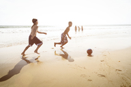 Side view of boys playing soccer on beach against clear sky - CAVF04831