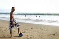 Portrait of boy standing with one leg on soccer ball at beach - CAVF04837