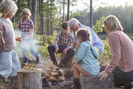 Grandparents and grandchildren enjoying campfire at lakeside - CAIF09421