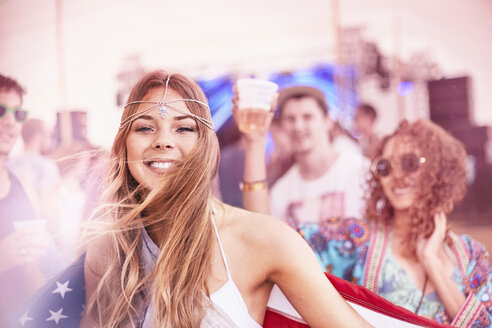 Portrait smiling young woman with American flag at music festival - CAIF09433
