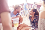 Young couple drinking beer and talking at music festival - CAIF09436