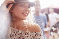 Close up smiling young blonde woman at music festival - CAIF09445