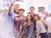 Young friends posing for selfie at music festival - CAIF09448
