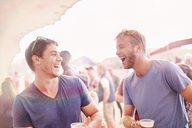 Young men drinking and laughing at music festival - CAIF09457