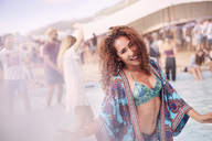 Portrait young woman dancing at poolside party - CAIF09460