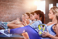 Young men and women with kettlebells in exercise class gym studio - CAIF09481