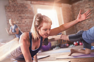 Young woman doing bird dog plank in exercise class gym studio - CAIF09487