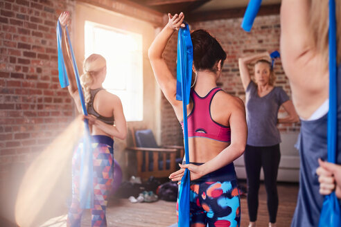 Women using resistance bands in exercise class gym studio - CAIF09490