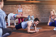 Young man and woman practicing stacked plank pose in gym studio - CAIF09496