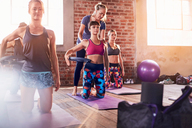 Fitness instructor helping young woman with pilates ring in exercise class gym studio - CAIF09514