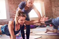 Fitness instructor helping young woman practicing bird dog plank in exercise class gym studio - CAIF09517