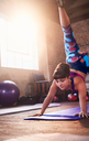 Young woman practicing scorpion dog yoga pose in gym studio - CAIF09520
