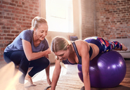 Fitness instructor helping young woman balancing on fitness ball in gym studio - CAIF09523