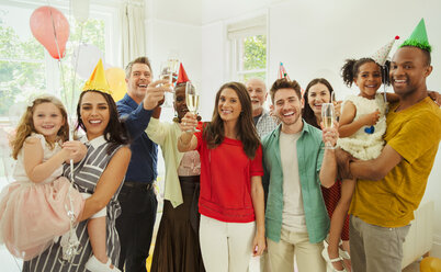 Portrait enthusiastic multi-ethnic multi-generation family celebrating party with champagne and party hats - CAIF09538