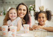 Portrait smiling mother and daughters at birthday party table - CAIF09547