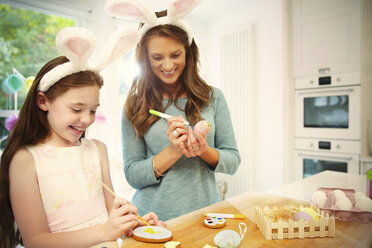 Mother and daughter wearing costume rabbit ears coloring Easter eggs and cookies - CAIF09550