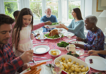 Multi-generation family eating at Christmas dinner table - CAIF09556