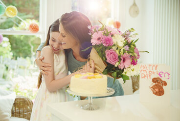 Affectionate daughter giving flower bouquet to mother on Mother's Day - CAIF09559