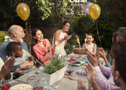 Multi-ethnic multi-generation family clapping celebrating birthday with fireworks cake at patio table - CAIF09562
