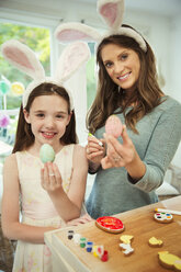 Portrait smiling mother and daughter wearing costume rabbit ears showing decorated Easter eggs - CAIF09565