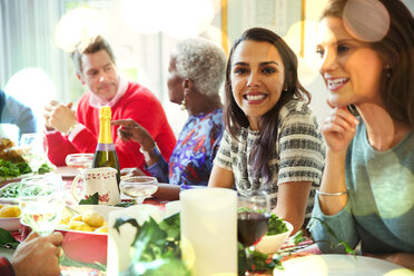Portrait smiling woman enjoying Christmas dinner at table - CAIF09568