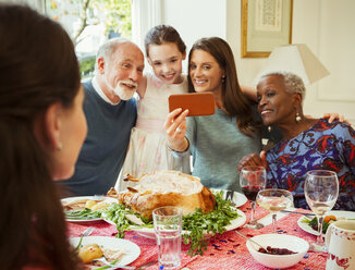 Multi-ethnic multi-generation family with camera phone taking selfie at Christmas dinner table - CAIF09571