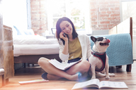 Woman talking on cell phone next to French Bulldog on floor - CAIF09667