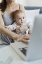 Mother holding baby daughter and working at laptop - CAIF09685