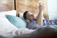 Man listening to music with headphones and mp3 player laying on bed - CAIF09688
