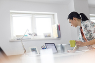 Businesswoman drinking coffee and working at laptop in office - CAIF09700