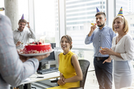 Business people celebrating birthday with cake in office - CAIF09715