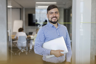 Portrait smiling businessman holding laptop in office - CAIF09724