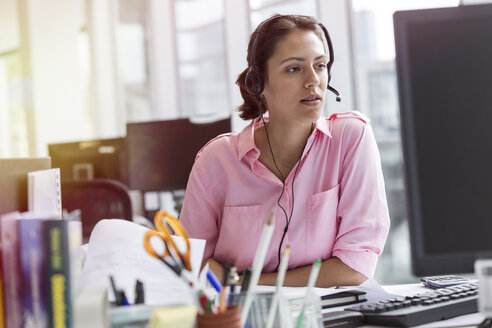 Businesswoman with hands-free device using computer in office - CAIF09754