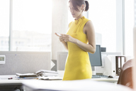Businesswoman texting with cell phone in office - CAIF09763