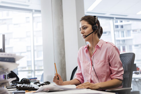 Businesswoman with hands-free device talking on telephone at office desk - CAIF09766
