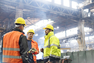 Steel workers talking in factory - CAIF09778
