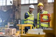 Steel workers talking and pointing in factory - CAIF09796