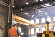 Steel worker with clipboard looking up in factory - CAIF09799