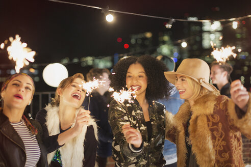 Young women with sparklers at rooftop party - CAIF09817