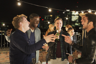 Young men drinking and laughing at rooftop party - CAIF09823