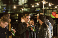 Young men drinking beer at rooftop party - CAIF09826