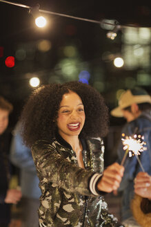 Enthusiastic young woman waving sparkler at rooftop party - CAIF09829