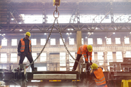 Steel workers fastening crane chain in factory - CAIF09832