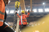 Steel workers fastening chain to crane in factory - CAIF09835